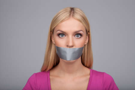She will not gossiping anymore. Portrait of beautiful young women with her mouth covered with an adhesive tape standing isolated on gray photo