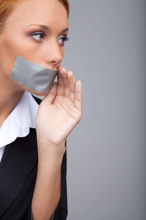 Businesswoman gossiping. Portrait of beautiful young businesswomen with her mouth covered with an adhesive tape standing isolated on gray and  holding her hand near mouth photo