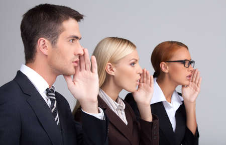 Global gossiping. Side view of three attractive young business people telling gossips standing with their hands covering mouth while isolated on gray photo