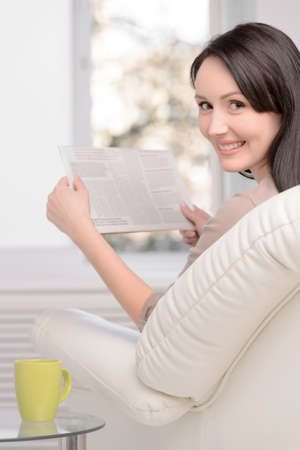 Only good news. Beautiful middle-aged woman sitting on the couch reading a Sunday paper photo