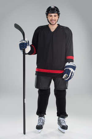 Attractive hockey player in uniform. Standing full length isolate on grey photo