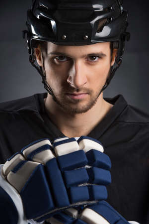 protective helmets: Portrait of handsome hockey player in black helmet. Isolated on black Stock Photo