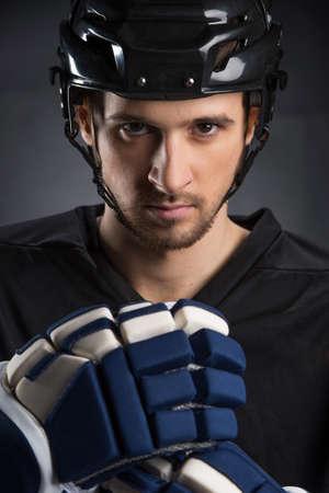 protective helmets: Ritratto di giocatore di hockey bello in casco nero. Isolato su nero