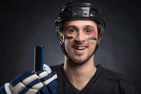 Lustige Eishockeyspieler lächelnd mit einem Zahn fehlt. Isoliert auf schwarz