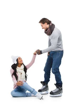 Careful man helping his girlfriend to stand up after falling on skating ring. Isolated on white photo