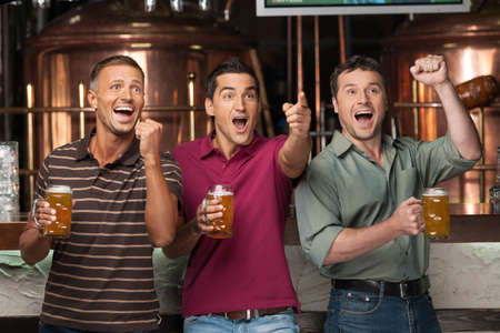 football party: Friends cheering. Three happy soccer fans drinking beer at the pub Stock Photo