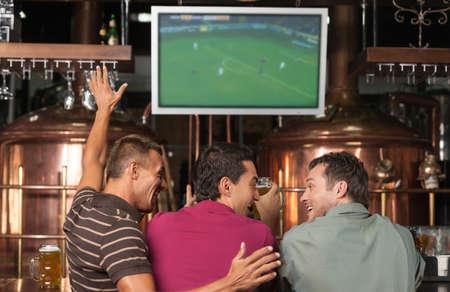 personas viendo television: Ventiladores de fútbol feliz. Tres felices fanáticos del fútbol viendo un juego en el pub