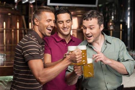 hombre tomando cerveza: Viejos amigos. Tres amigos felices bebiendo cerveza en el pub Foto de archivo