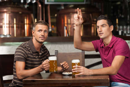 Što biste radili s osobom iznad, prikaži slikom - Page 23 23778790-one-more-beer-please-two-friends-drinking-beer-at-the-pub-while-one-of-them-asking-a-waiter-