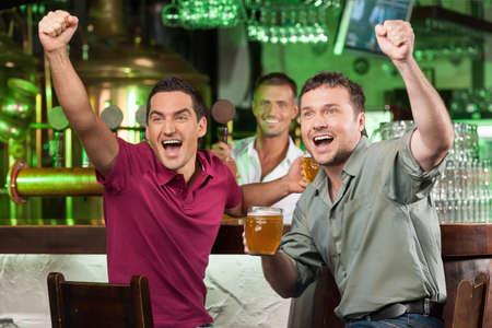 Fußball-Fans an der Theke. Zwei glückliche Fußball-Fans jubeln in der Bar und trinken Bier, während Barkeeper serviert Bier im Hintergrund