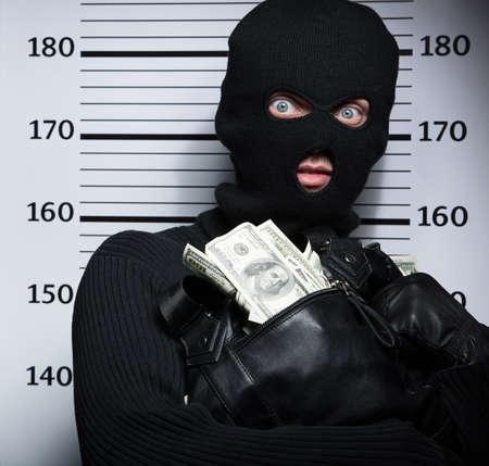 逮捕された泥棒。警察の整列に対して立っている間盗まれた商品と袋を持って怒っている泥棒