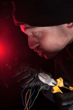 criminal activity: Cutting the wires. Close-up of frustrated burglar cutting the wires Stock Photo