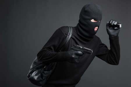Thief. Side view of men in black balaclava holding a gun and flashlight while standing isolated on black photo