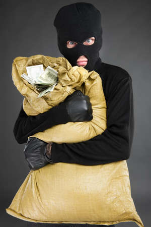 Thief with stolen goods. Front view of frustrated men in black balaclava holding a stolen money bag while standing isolated on grey photo