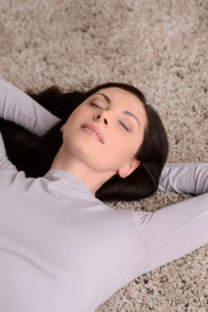 lying on back: Just doing nothing. Top view of beautiful middle-aged women lying on the floor with her eyes closed