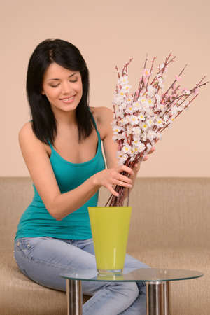 Beautiful girl with flowers. Beautiful young woman arranging flowers into the vase
