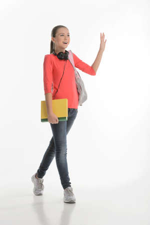 bookbag: Hi guys! Happy teenage schoolgirl greeting someone while standing isolated on white