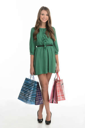 Teenage girl shopping. Full length of pretty teenage girl holding shopping bags and smiling while isolated on white photo