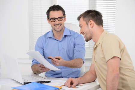 Große Zahlen! Zwei fröhliche Geschäftsleute dicussing etwas auf dem Papier und lächelt