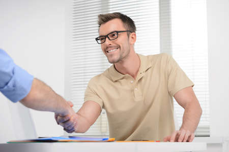 hand shake: Welcome on board! Young cheerful businessman shaking someone� hand and smiling