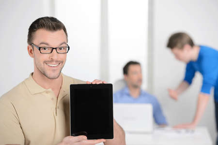 Men with digital tablet. Happy young businessman holding a digital tablet and smiling while colleagues working on the background photo