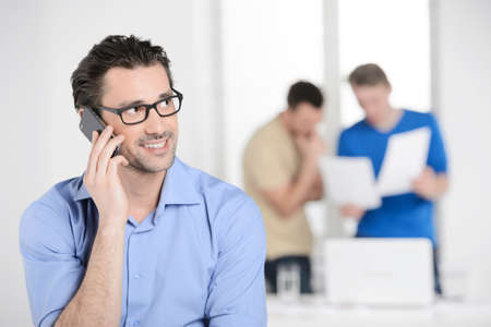 Businessman talking on the phone. Confident young businessman talking at the phone and smiling while colleagues working on the background photo