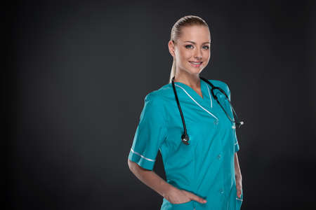 Young Blond nurse in green robe standing isolated over black background. Smiling and looking at camera photo
