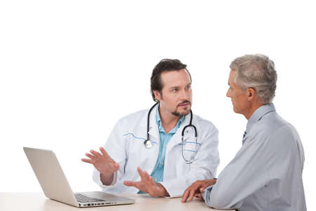 Adult doctor talking to old patient. Showing something on laptop
