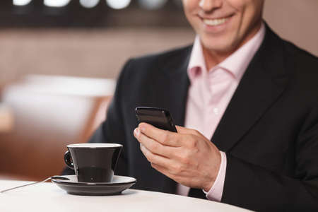 Businessman typing a message. Cropped image of businessman drinking coffee and typing a message in his mobile phone photo
