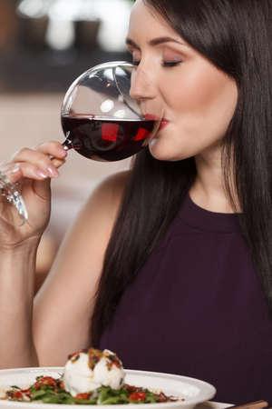 Good wine. Portrait of beautiful mature women drinking wine in restaurant photo
