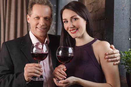 Loving couple. Cheerful middle-aged couple holding glasses with wine and smiling at camera photo