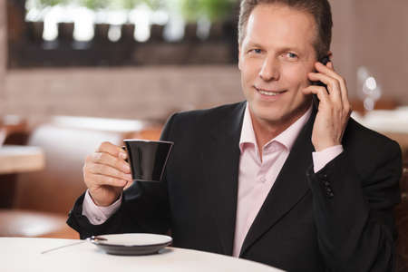 Talking to business partner. Cheerful businessman drinking coffee and talking at phone while sitting at restaurant photo