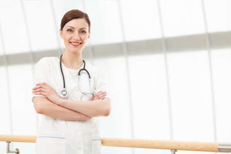 positiv: Positiv and caring doctor. Beautiful young female doctor standing with her arms crossed Stock Photo