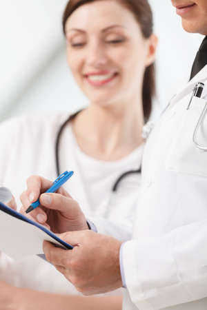 Going through a report. Close-up of two medical doctors writing in the writing pad together Stock Photo - 23809987