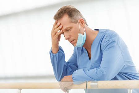 Frustrated doctor. Depressed mature doctor in blue uniform standing with his hand in hair photo