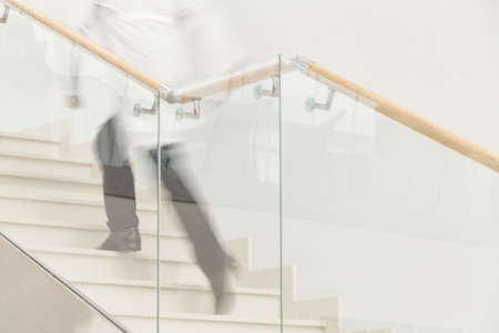 Hurry to save a life. Blur motion of doctor in white uniform hurrying and running upstairs photo