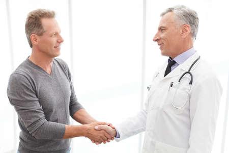 happy patient: Thankful patient. Thankful mature patient shaking doctors hand