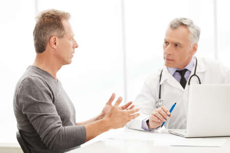 male doctor: Doctor and patient. Doctor listening to the patient while he is telling about his problems