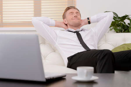 Relaxing after hard working day. Cheerful young businessman relaxing on the couch with his eyes closed photo