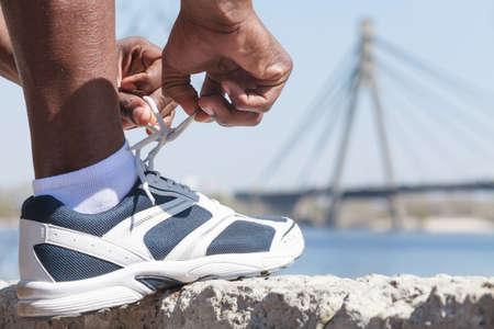 vistiendose: Atar los cordones de los zapatos. Hombres decsent africanos atar sus cordones Foto de archivo