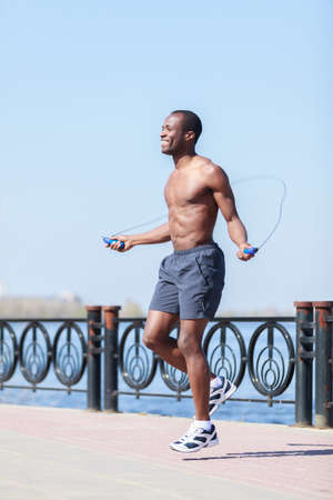 Man jumping on the jumping rope. Young african decsent men with naked torso jumping on the jumping rope outdoors photo