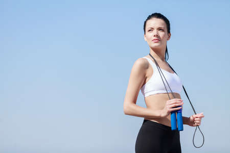 woman rope: Women with jumping rope. Beautiful young women standing with a jumping rope in her hands with a sky as background Stock Photo