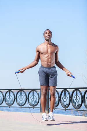 Trainings everyday. Young african decsent men jumping on the rope Stock Photo - 23926787