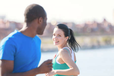 Friends meeting. Young couple smiling to each other while jogging on the street photo