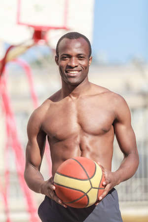 Want to play? Young african decsent men with naked torso holding a ball in his hand with a basketball hoop on the background Stock Photo - 23926788