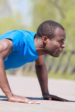 Doing push-ups. Side view of young african men doing push-ups Stock Photo - 23926809