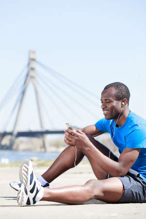 Relaxing after training. Young african men sitting outdoors with his MP3 player and listening to the music Stock Photo - 23926811