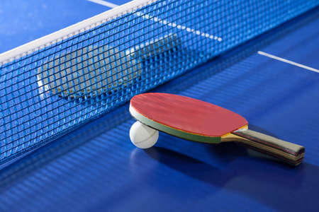 table tennis: Table tennis rackets. Top view of table tennis racket lying on the tennis table on the both sides of net Stock Photo