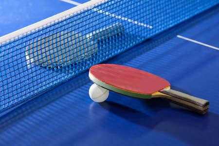 tischtennis: Tischtennisschl�ger. Top-Blick auf Tischtennisschl�ger, die auf dem Tennisplatte auf den beiden Seiten des Netto