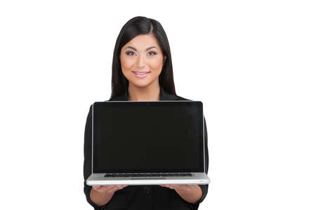 Nice looking Indian girl showing laptop. Holding laptop while standing isolated on white photo